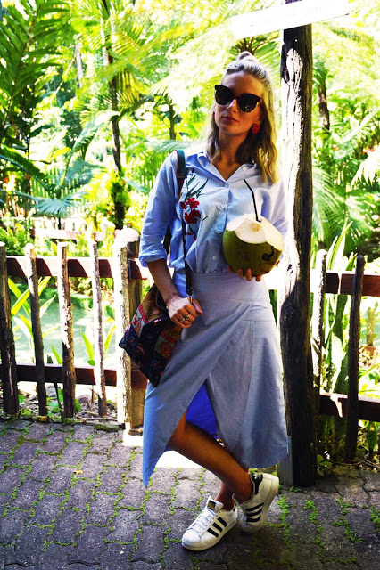 folk style floral embroidered stripe shirt outfit with wrap skirt and oversized cat eye sunglasses in Kuranda girl drinking coconut