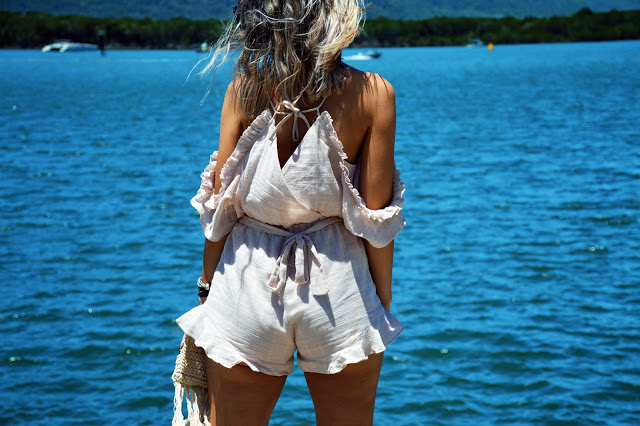 blonde windswept hair and a ruffled off shoulder summer playsuit