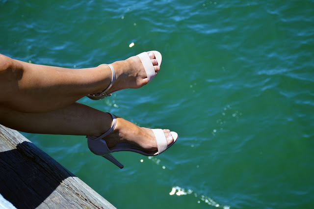 nude heels photographed over blue water