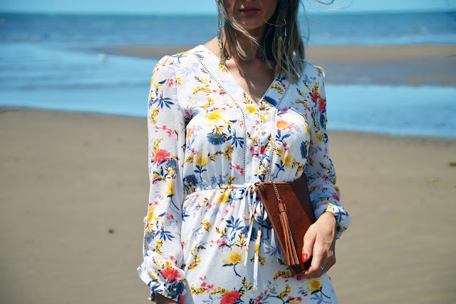 white floral shirt dress and tassel tan clutch bag on beach