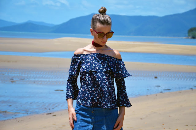 girl on Cairns beach wearing off shoulder floral ruffle top with red velvet choker and cat eye sunglasses
