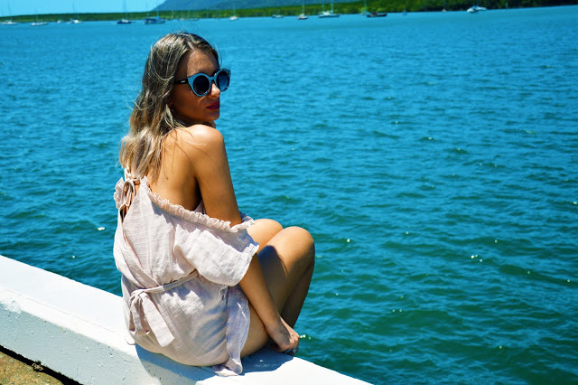 girl wearing a ruffled playsuit looking out to a beautiful blue tropical ocean