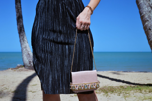 pleated black skirt and embellished nude bag