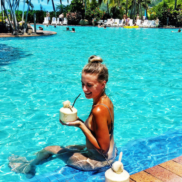 girl drinking pina colada in coconut in pool