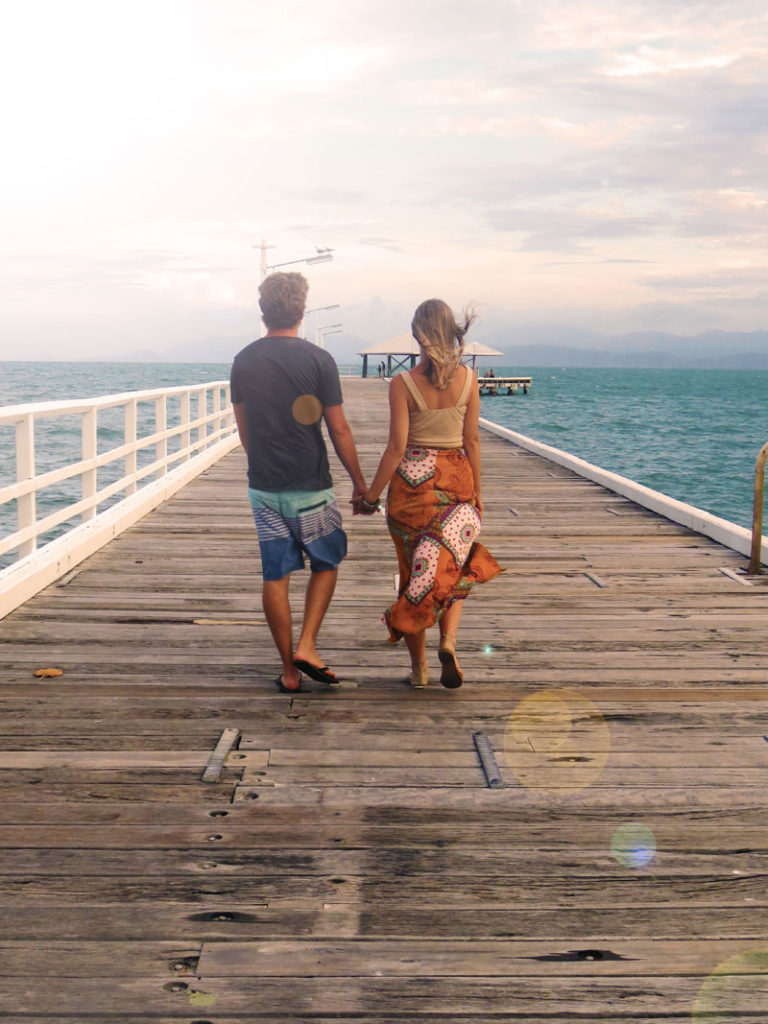 couple walking along pier hand in hand