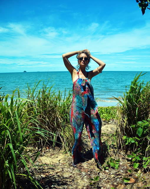 boho girl on beach wearing printed jumpsuit