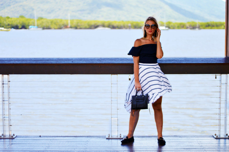 fashion blogger wearing striped skirt gucci style loafers off shoulder top and prada cinema sunglasses
