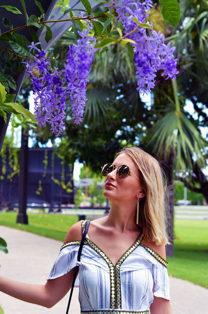 off shoulder playsuit styled with tassel earrings and round sunglasses