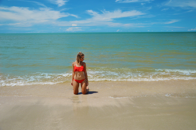 tanned blonde girl in red scallop edge bikini on tropical four mile beach port douglas australia