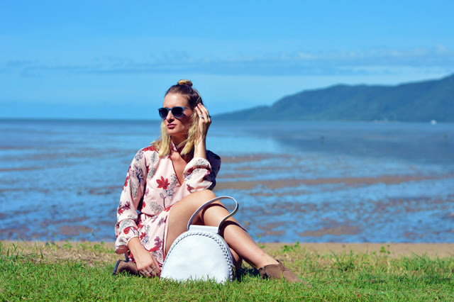 blogger spring summer transitional outfit blush floral dress and grey statement handbag in front of ocean
