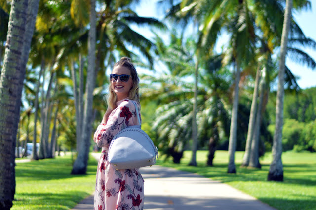 girl with blonde topknot lob wearing floral blush dress with grey oliver bilou handbag in front of palm trees