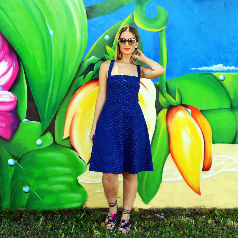 summer outfit idea navy lace dress statement earrings pom pom sandals in front of tropical graffiti wall