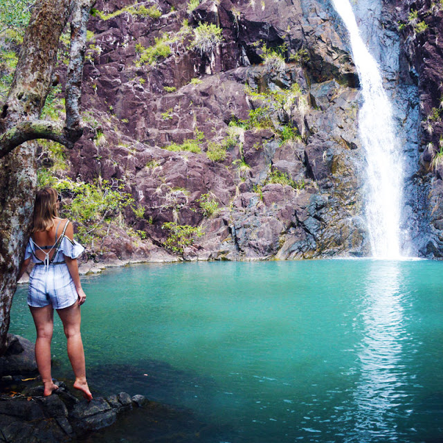 boho girl in playsuit stood in front of stunning blue tropical waterfall