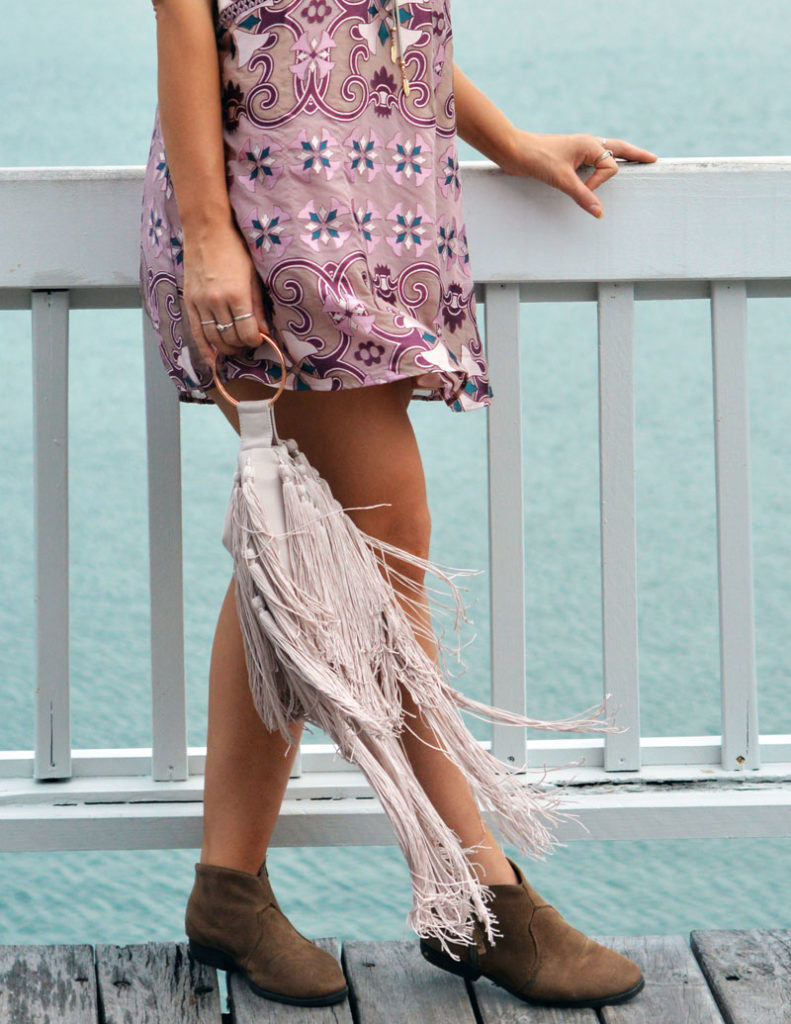 close up of outfit details mauve boho print dress fringe clutch and beige suede ankle boots