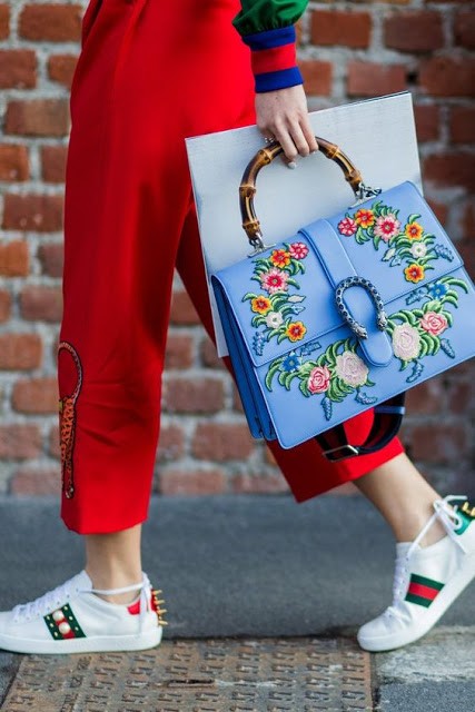 street style look with embroidered gucci dionysus bag and gucci embroidered trainers and embroidered leopard red pants