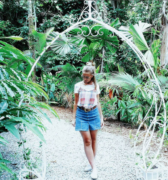 fashion blogger walking through tropical rainforest wearing denim skirt tartan cami
