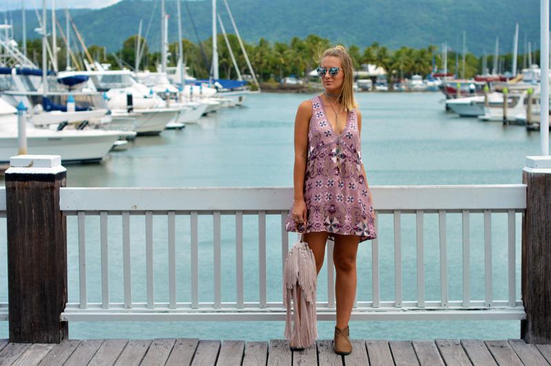 blonde fashion blogger wearing mauve boho floral print dress fringe bag beige ankle boots