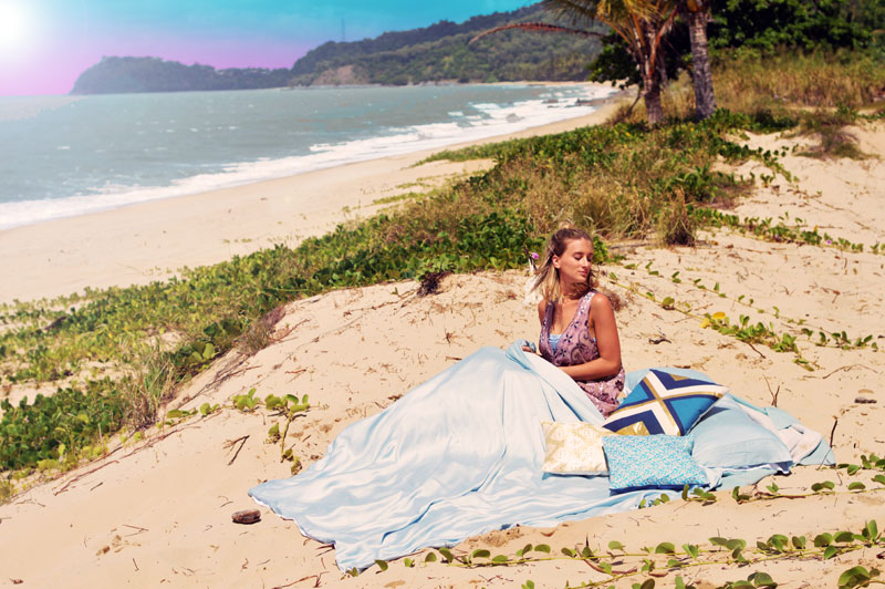girl in boho beach bed set up on tropical far north queensland secret spot watching sunrise