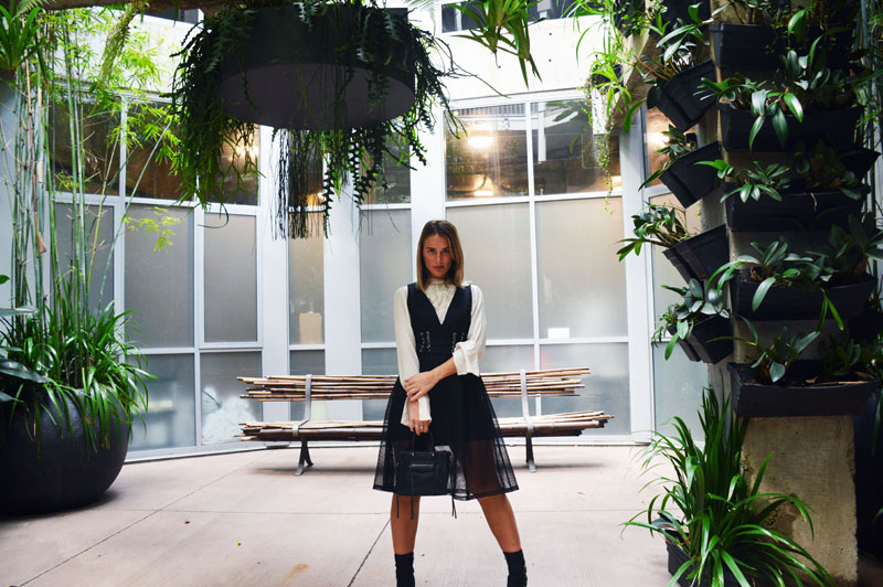 fashion blogger wearing lace up black mesh dress over white shirt in industrial chic lobby of urban newtown with hanging plants