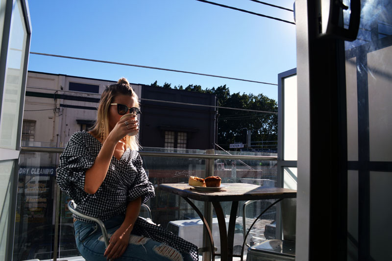 fashion blogger wearing gingham wrap blouse prada sunglasses drinking coffee on balcony