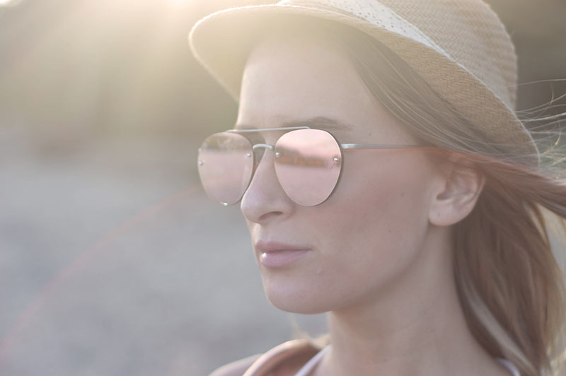 close up of fashion blogger girl wearing rose gold sunglasses and straw hat on beach