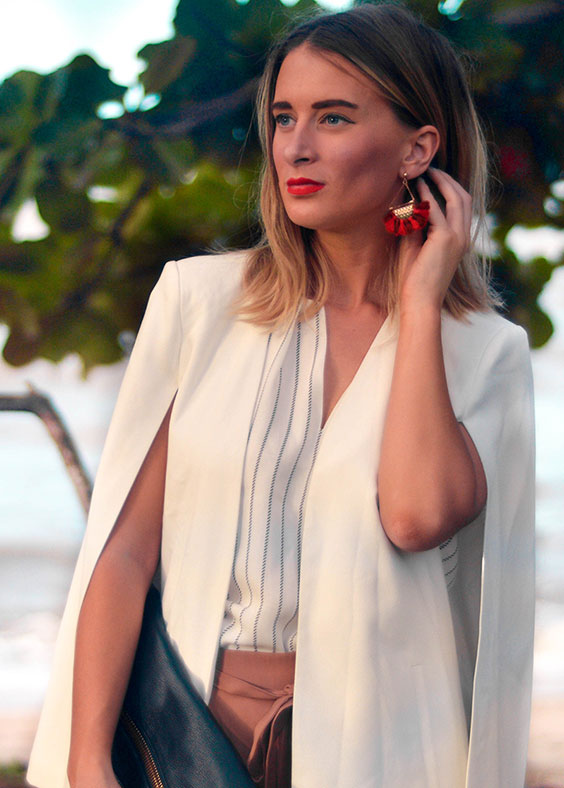 blonde girl wearing red lipstick red tassel earrings and white cape blogger outfit