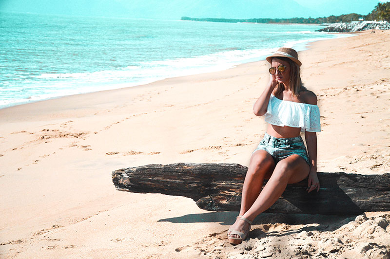 vacation holiday summer beach outfit off shoulder white top denim shorts wedge heels and hat on far north queensland cairns beach