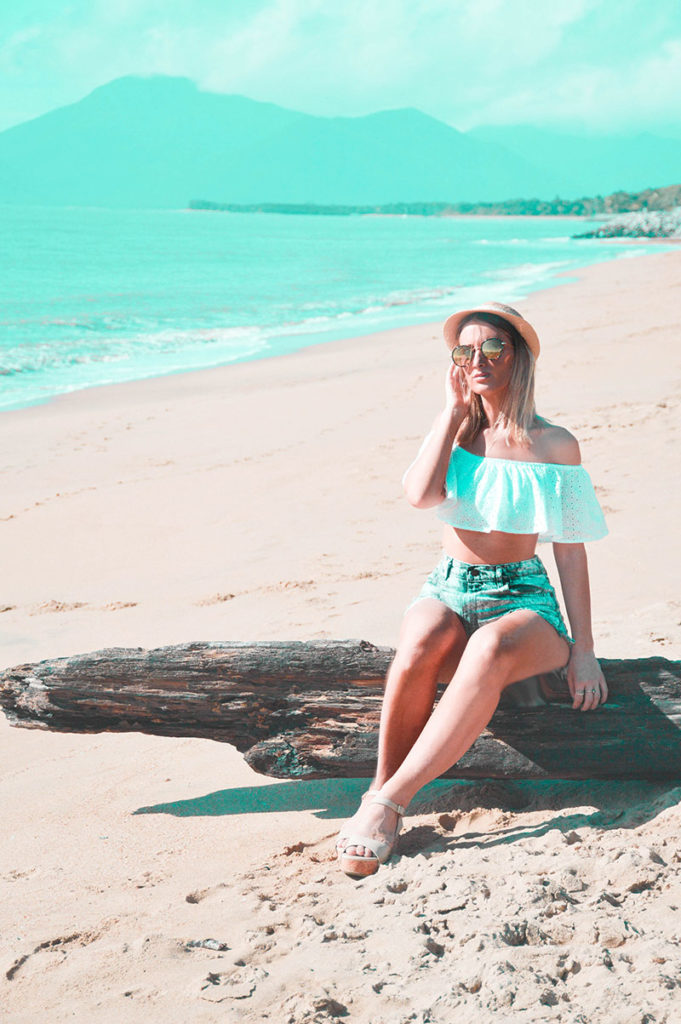 summer beach outfit off shoulder white top denim shorts wedge heels and hat on far north queensland cairns beach