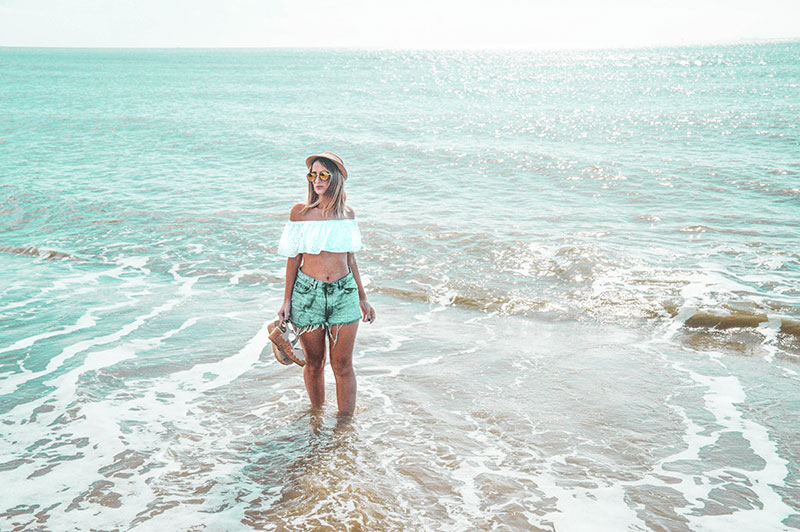 blonde australian blogger stood in tropical sea in crop top and denim shorts