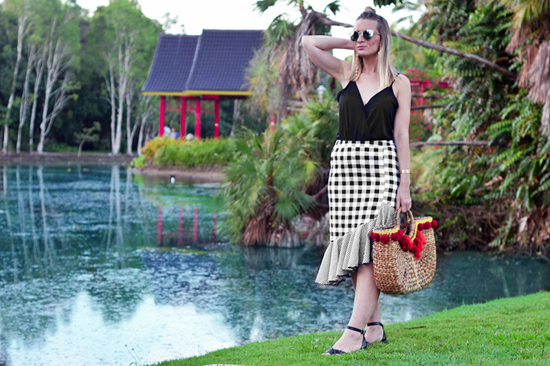 australian fashion blogger wearing ruffle hem gingham skirt and pom pom basket bag at cairns chinese friendship garden botanical garden