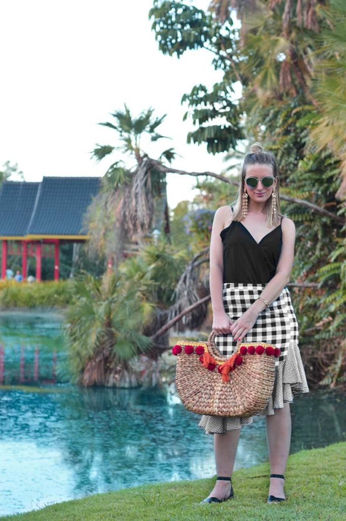 summer outfit idea gigham ruffle skirt with black top and pom pom basket bag at cairns centary lakes