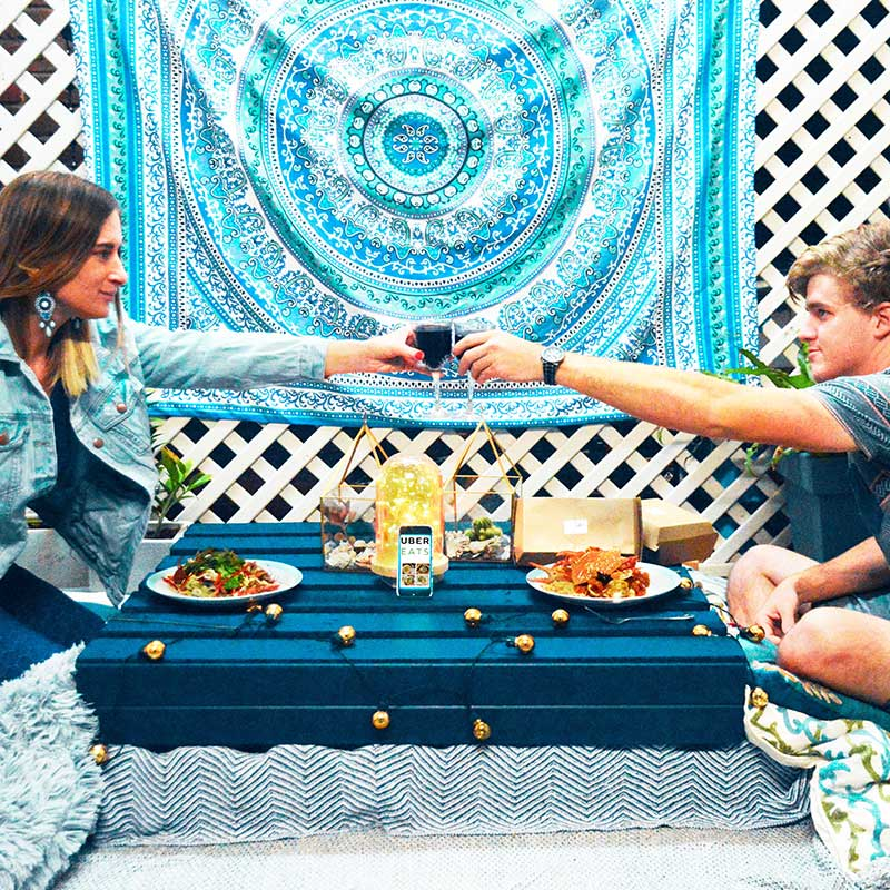couple enjoying a home dinner date night in diy boho outdoor eating area