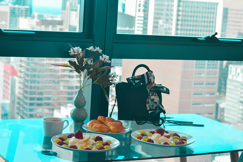 fruit salad and croissant breakfast in melbourne hotel looking over city view