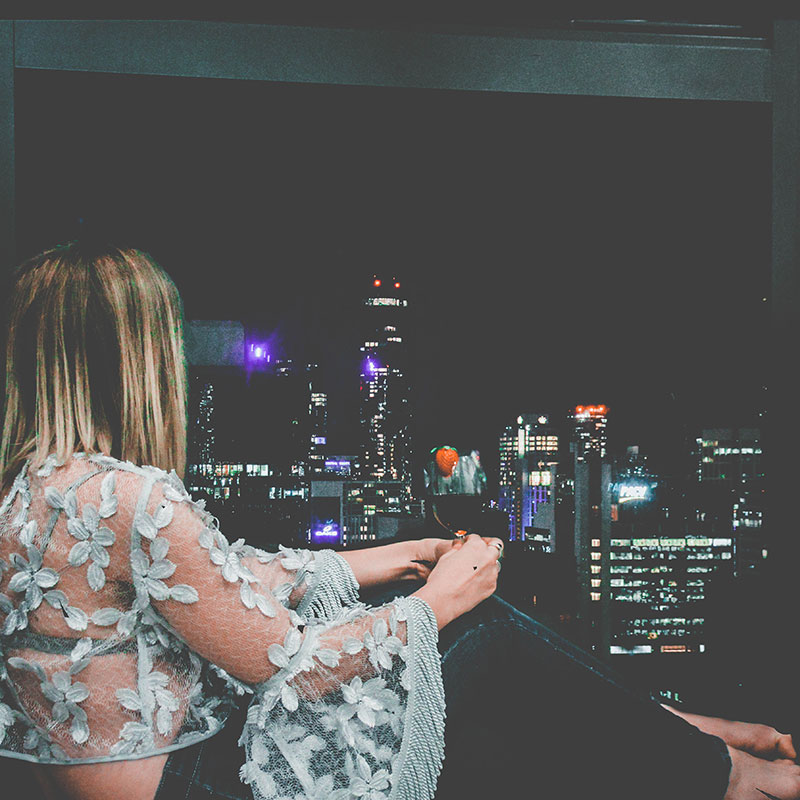 fashion blogger looking out of hotel room window at melbourne city night sky