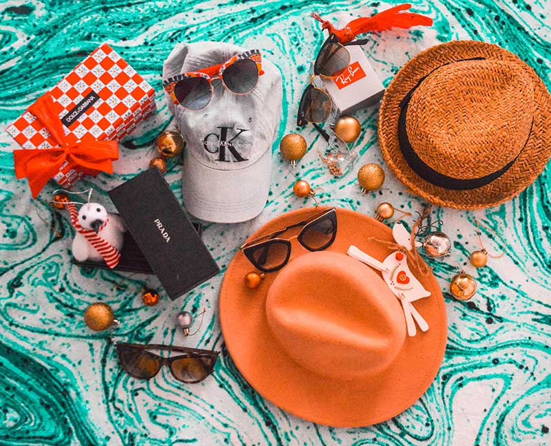 beach babe christmas gift guide flatlay with hats calvin klein cap sun hat dolce gabbana sunglasses prada sunglasses ray ban clubmaster sunglasses