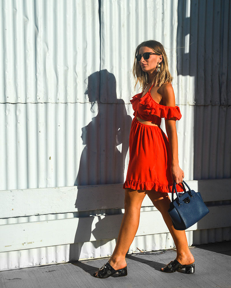australian fashion blogger the daily luxe wears off shoulder ruffle cut out red dress brocade pearl embellished mules and navy handbag