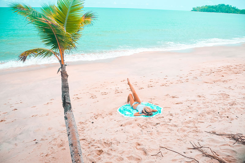 girl lying on round towel on tropical north queensland cairns beach australia
