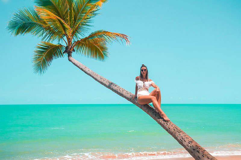 girl sitting on palm tree on tropical paradise beach wearing white off shoulder ruffle polkadot swimsuit cairns fashion blogger the daily luxe