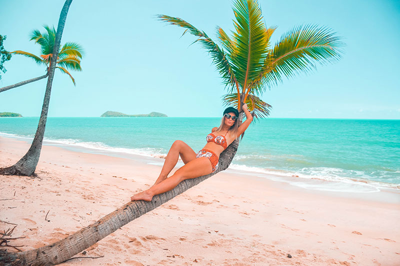 girl lying on palm tree on tropical beach wearing retro style floral bikini baker boy hat prada sunglasses on tropical north queensland cairns beach