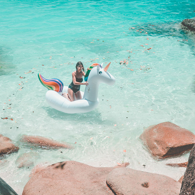 girl on inflatable unicorn fitzroy island cairns inflatable rainbow unicorn australia instagram