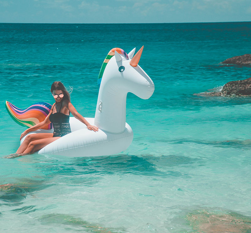 the daily luxe fashion blogger on inflatable rainbow unicorn in summer wanderlust ocean