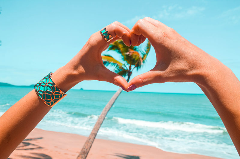 wanderlust boho beach shot aqua rose gold boho jewellery hand heart in front of tropical australian beach clifton beach cairns
