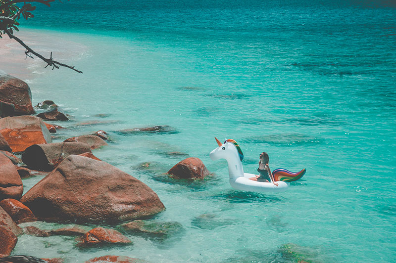 inflatable rainbow unicorn instagram in tropical ocean fitzroy island australia
