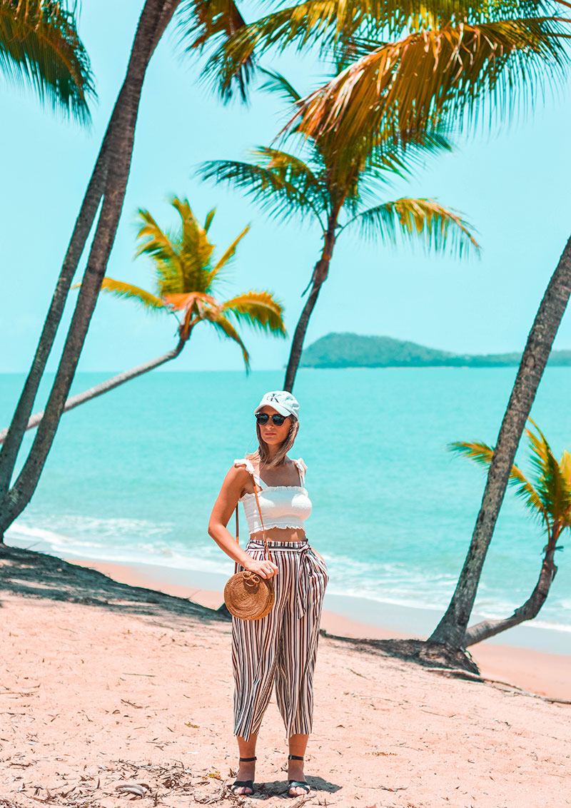 the daily luxe wearing white shirred crop top pinstripe culottes round rattan basket bag calvin klein denim baseball cap on cairns beach summer outfit idea