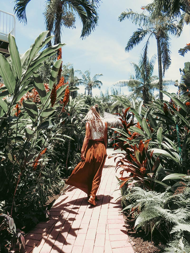 boho fashion blogger wearing maxi skirt lace crop top in tropical setting