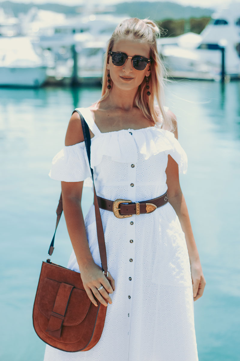white dress outfit off shoulder dress gold buckle belt tan leather bag