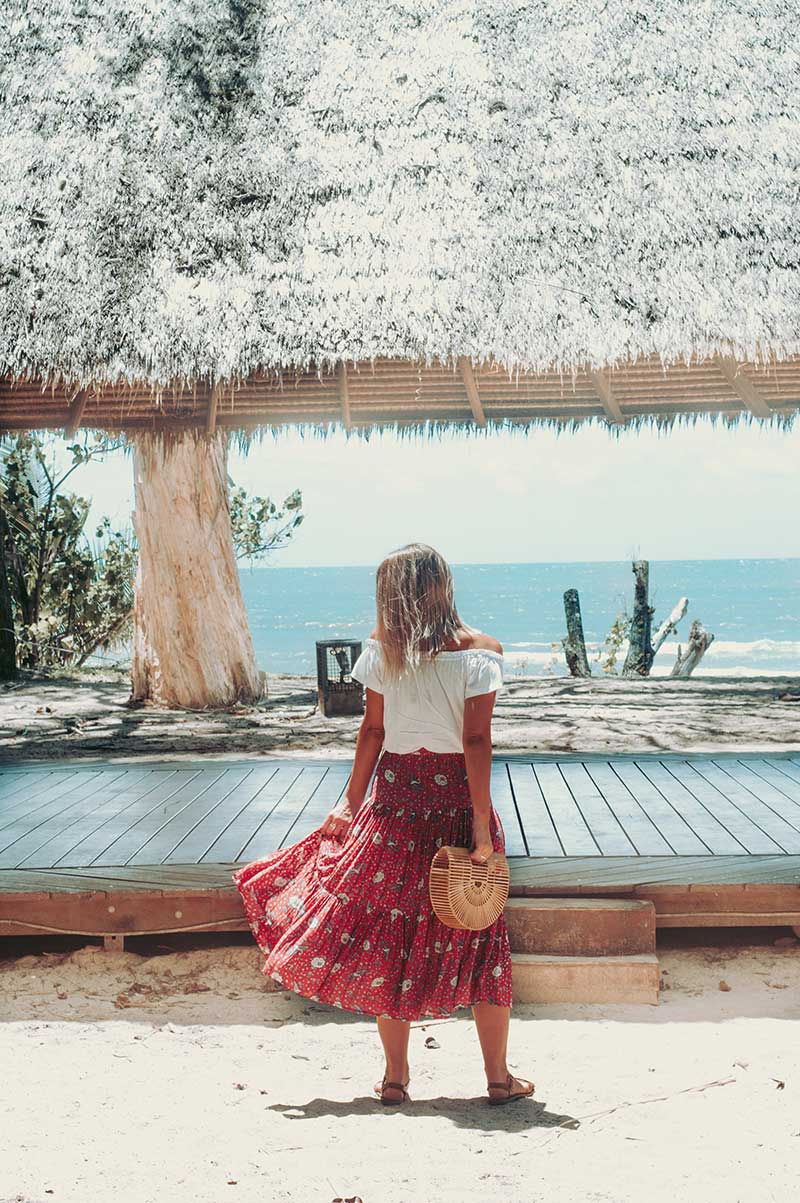 summer boho outfit instagram floral printed maxi skirt off shoulder white top cult gaia bag on beach