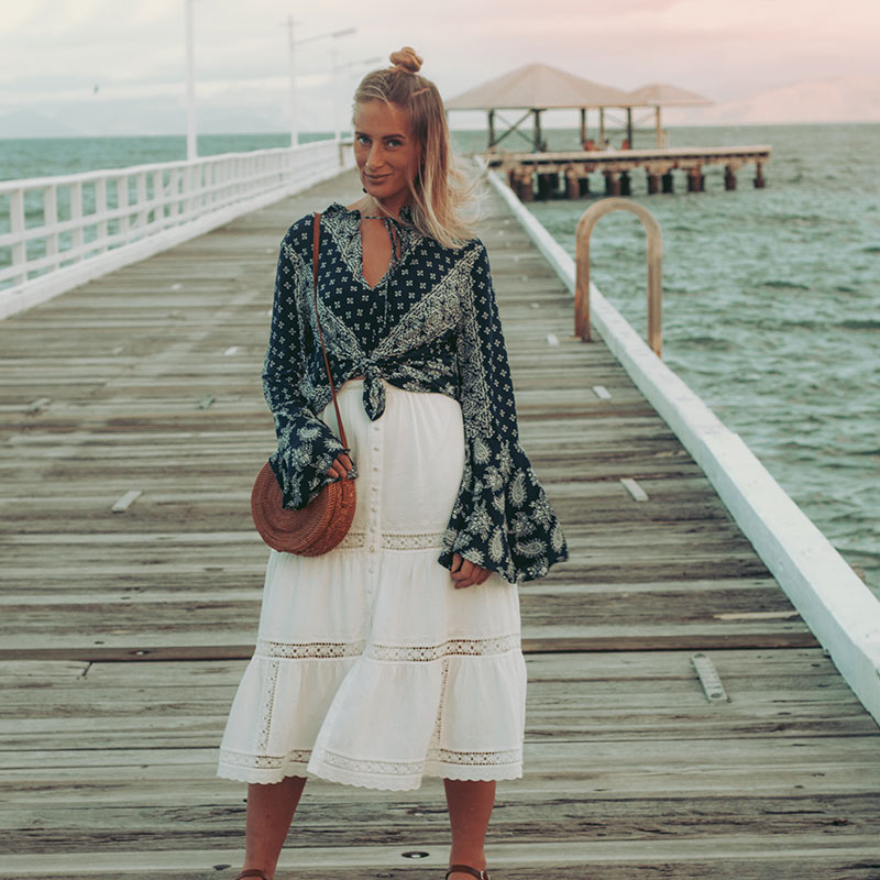the wandering coast bell sleeved top with arnhem white lace midi and basket bag photographed on Picnic Bay jetty at sunset