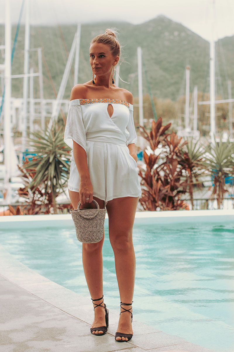 the wandering coast festival of the sun romper with statement earrings woven basket bag and black heels