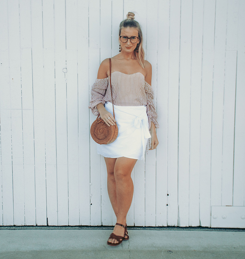 summer blogger outfit the daily luxe wears cat eye prescription glasses off shoulder pinstripe top white linen wrap skirt